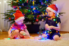 Two little sisters decorating a Christmas tree Royalty Free Stock Photos