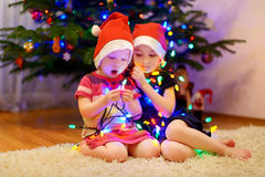 Two little sisters decorating a Christmas tree Royalty Free Stock Images
