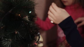 Two little sisters decorating Christmas tree with fir-cone. New year preparation. Happy girls and family. Little girls in comfortable home clothes sitting on stock video