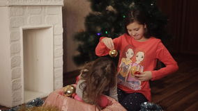 Two little sisters decorating Christmas tree with fir-cone. New year preparation. Happy girls and family. Little girls in comfortable home clothes sitting on stock video footage
