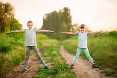 Two little sisters doing exercise outdoors. Healthy lifestyle royalty free stock images