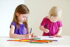Two little sisters drawing with colorful pencils. Two cute little sisters drawing with colorful pencils at a daycare stock photo