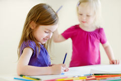 Two little sisters drawing with colorful pencils. Two cute little sisters drawing with colorful pencils at a daycare stock photos