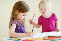 Two little sisters drawing with colorful pencils Stock Image