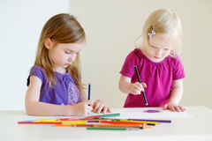 Two little sisters drawing with colorful pencils Royalty Free Stock Photo