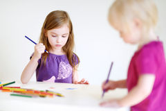 Two little sisters drawing with colorful pencils. Two cute little sisters drawing with colorful pencils at a daycare royalty free stock image