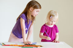 Two little sisters drawing with colorful pencils Stock Photo