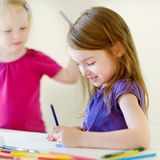 Two little sisters drawing with colorful pencils Royalty Free Stock Photos