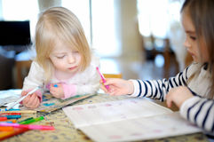 Two little sisters drawing and learning together Royalty Free Stock Photography
