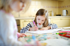 Two little sisters drawing and learning together Stock Photo