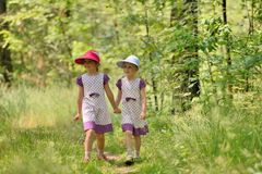 Two little sisters in a dress and hat on a walk in forest Stock Photography