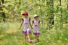 Two little sisters in a dress and hat on a walk in forest Royalty Free Stock Images