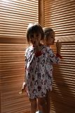 Two little sisters dressed in the pajamas are hiding in the closet with wooden doors.  royalty free stock photo