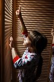 Two little sisters dressed in the pajamas are hiding in the closet with wooden doors royalty free stock image