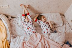 Two little sisters dressed in pajamas sleeping in the bed in the bedroom stock photography