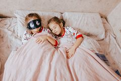 Two little sisters dressed in pajamas sleeping in the bed in the bedroom stock photos