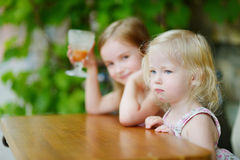 Two little sisters drinking orange juice in cafe Stock Image