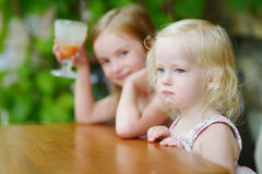 Two little sisters drinking orange juice in cafe Royalty Free Stock Photography
