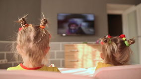 Two little sisters eat at the table and have fun watching cartoons on TV. Back view. Two little sisters eat at the table and have fun watching cartoons on TV stock footage
