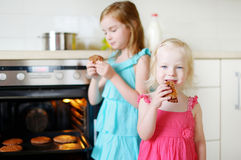 Two little sisters eating freshly baked cookies Stock Photos