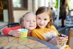 Two little sisters eating ice cream in an outdoor cafe Royalty Free Stock Images