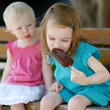 Two little sisters eating ice cream Stock Images