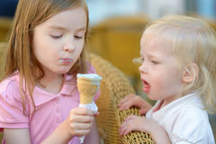 Two little sisters eating ice cream outdoors Stock Photos