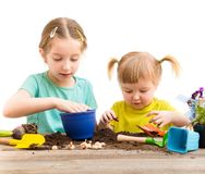 Two little sisters are engaged in gardening Stock Photos
