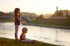 Two little sisters enjoying a view at sunset Stock Photo