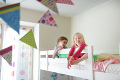 Two little sisters fooling around, playing and having fun in twin bunk bed Stock Photo