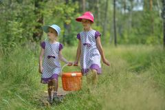 Two little sisters in forest with pannier for picnic Stock Photo