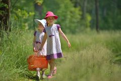 Two little sisters in forest with pannier for picnic Stock Photos