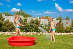 Two little sisters frolicing, splashing and having Royalty Free Stock Photos