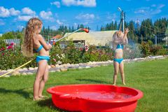 Two little sisters frolicing, splashing and having Stock Photo