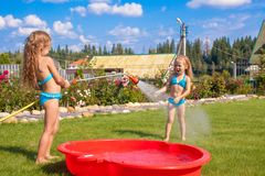 Two little sisters frolicing, splashing and having Stock Image