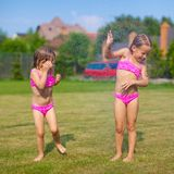 Two little sisters frolicing and splashing in Stock Images