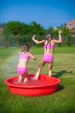 Two little sisters frolicing and splashing in Stock Photo