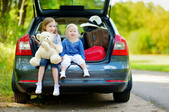Two little sisters going to a car vacation Royalty Free Stock Photography