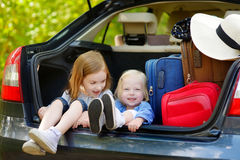 Two little sisters going to a car vacation Royalty Free Stock Image