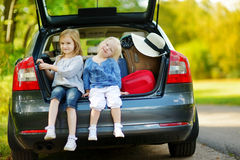 Two little sisters going to a car vacation Royalty Free Stock Photos
