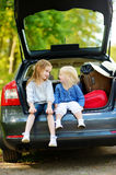 Two little sisters going to a car vacation Stock Image