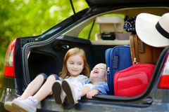 Two little sisters going to a car vacation Royalty Free Stock Photo