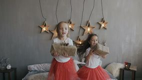 Two little sisters have fun jumping on the bed and holding Christmas gifts in their hands. On a gray wall hangs 6. Decorative wooden stars that shine with stock video footage