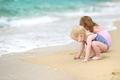 Two little sisters having fun on a beach Stock Image