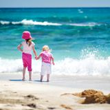 Two little sisters having fun on a beach Royalty Free Stock Photo