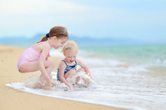 Two little sisters having fun on a beach Stock Images