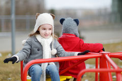 Two little sisters having fun on a playground Stock Photos