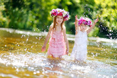 Two little sisters having fun by a river Stock Photos