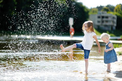 Two little sisters having fun by a river Stock Photography