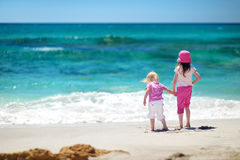 Two little sisters having fun on a sandy beach Stock Photos
